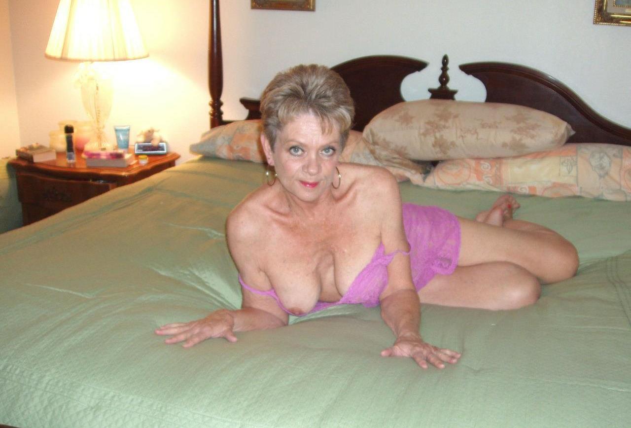 Signora anziana seminuda sdraiata a letto